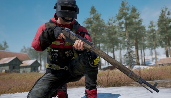 A PUBG character holding an old sniper rifle and kneeling on one knee