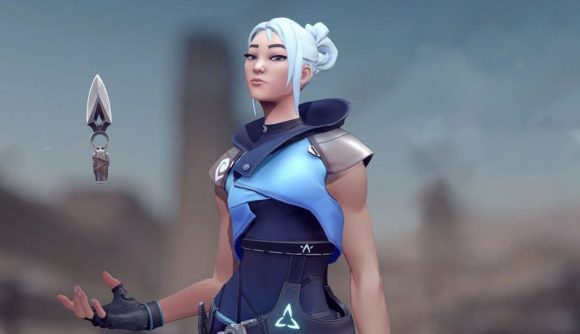 Valorant character Jett stands in front of a blurred background, nonchalantly juggling a kunai in her hand