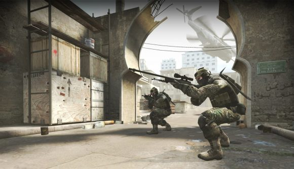 Two soldiers crouch between buildings in CS:GO, one aims a sniper rifle