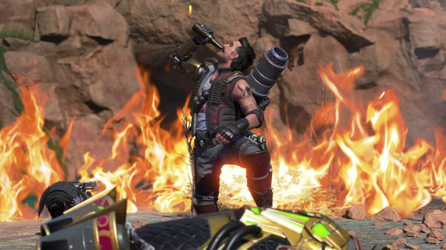 Fuse, the latest addition to Apex Legends, downs a bottle of beer on one knee in front of a wall of flames