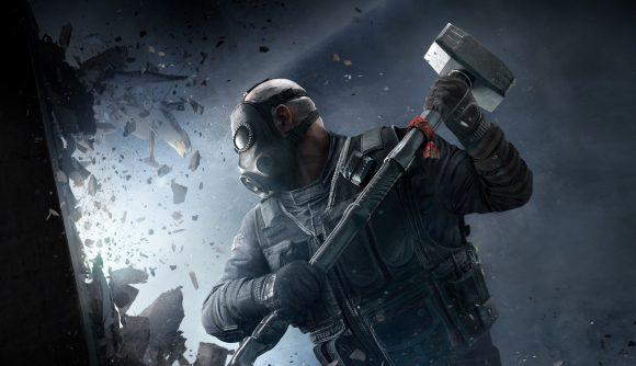 Rainbow Six Siege operator uses a sledgehammer to smash through a wall