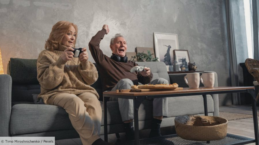Two elderly people dressed in beige sit on a sofa holding a gamepad. The man cheers, the woman claps