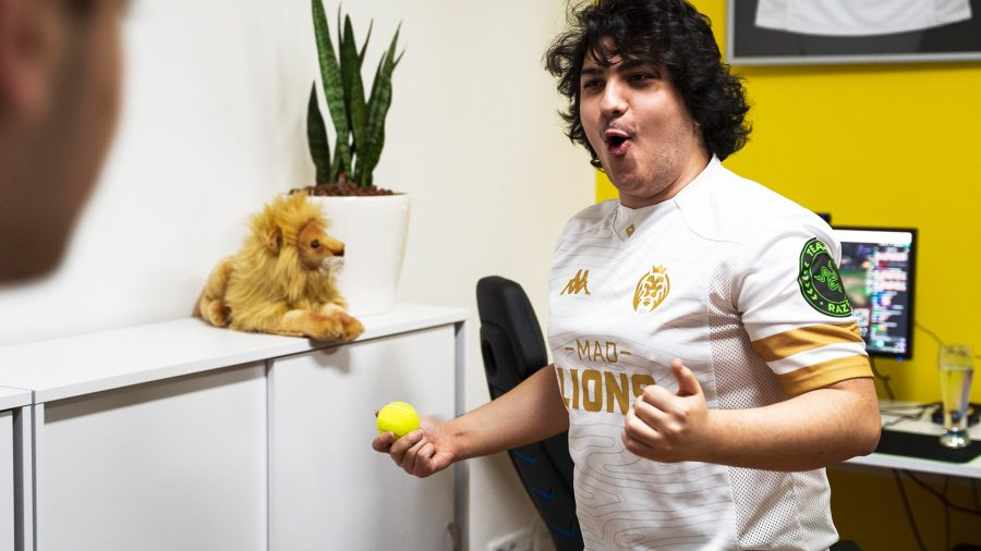 A long-haired man in a white jersey with gold details. There is a stuffed lion on the counter at the back next to a potted plant