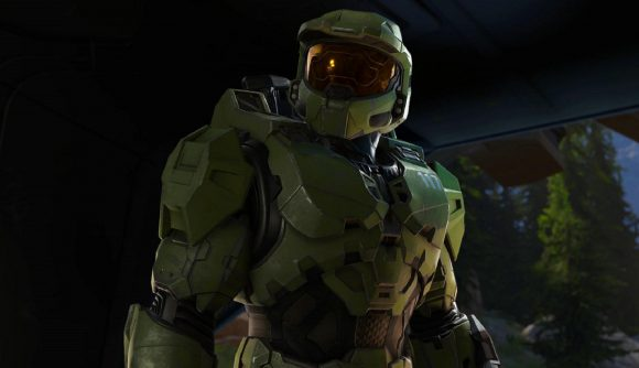 Master Chief stands in a cave and looks to the left of camera