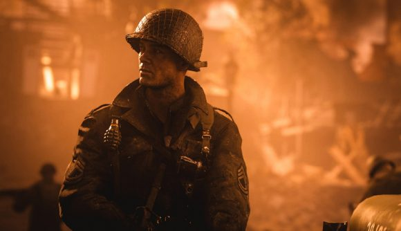 A World War 2 soldier stands in front of a burning building