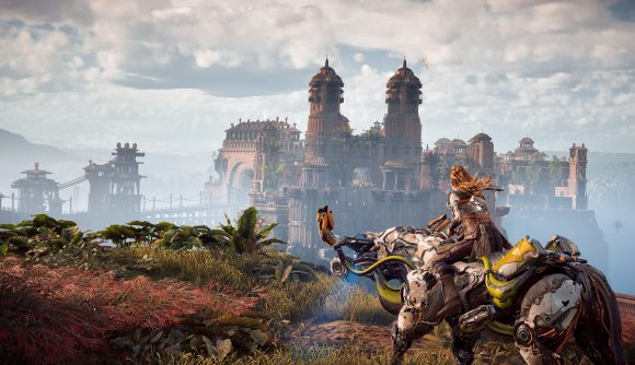 Aloy rides a mechnical steed and look to the distance, which sees a ruined castle stand across a ravine