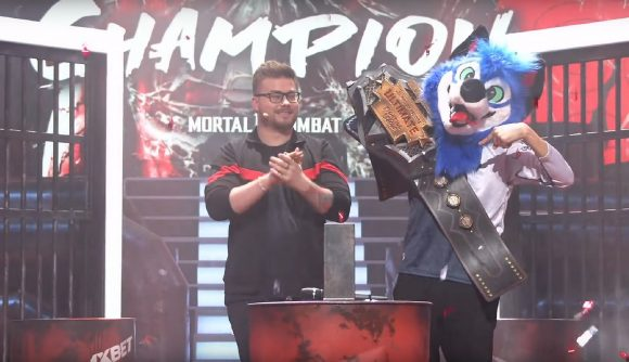 SonicFox lifts the WUFL champions belt while wearing their blue fursuit fox head