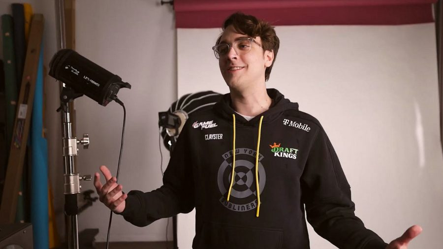 Call of Duty pro Clayster, wearing a black hoodie with yellow hood strings, with his arms outstretched