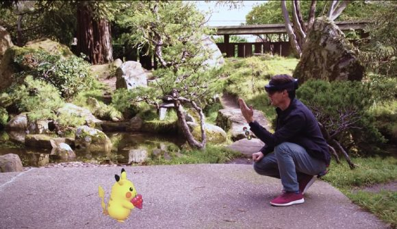 A man squats down wearing chunky VR glasses, Pikachu eats a berry in front of him. A real garden is the background