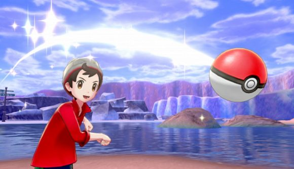 A Pokémon trainer throws a PokéBall, a lake is in the background