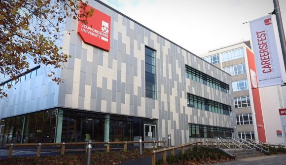 Staffordshire University's campus in Stoke on Trent. A grey and white building with a red sign showing the name of the university