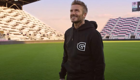 David Beckham, standing in the middle of a football field, wearing a black Guild hoodie