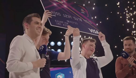 Two FIFA players lift up a giant cheque after winning a tournament