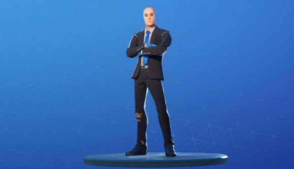 A mannequin figure in a suit with a blue tie stands with his arms crossed in front of a blue background