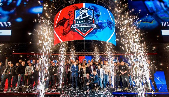 Players and casters gather on stage in front of red and blue banners as pyrotechnics shower them in sparks