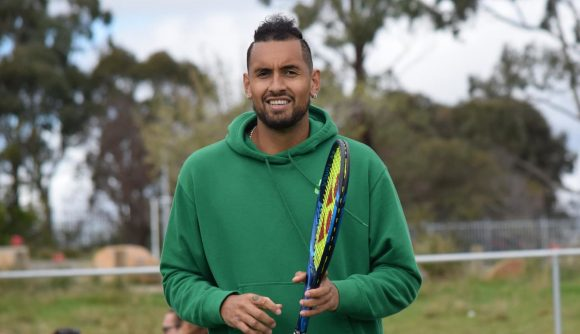 Nick Kyrgios in a green hoodie holding a blue and black tennis racket with yellow string