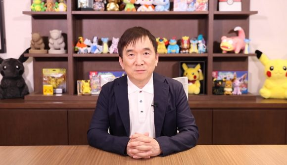 President Ishihara of the Pokémon Company sits at a desk staring at the camera, Pokémon plushies line the shelves behind him