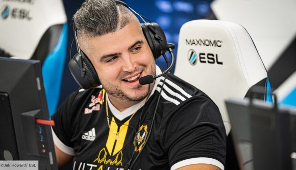 CS:GO pro RpK looking over to a teammate and smiling. He's wearing a black headset and a black Vitality jersey
