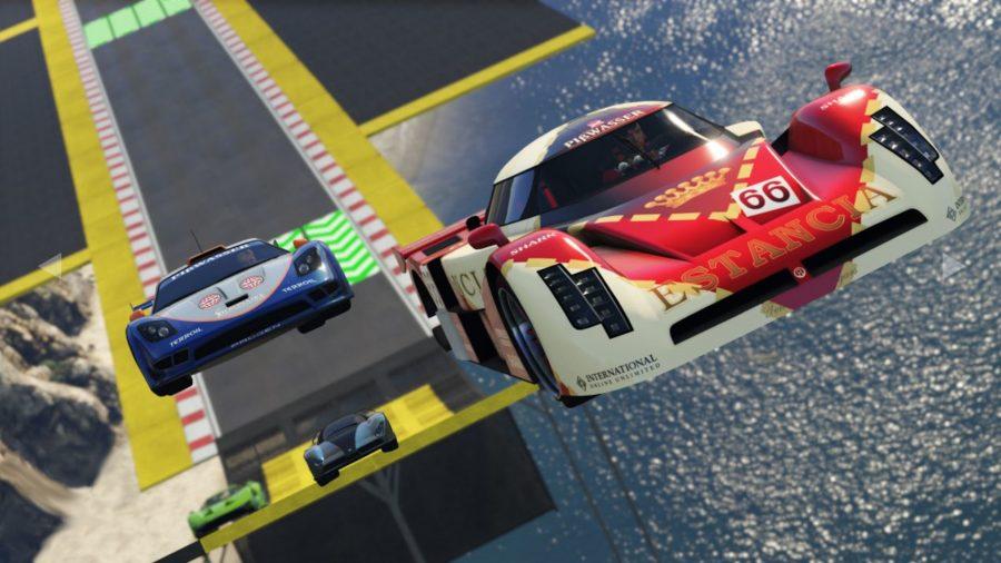 Two race cars speed along a GTA racetrack