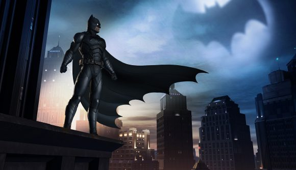Batman looks over the streets of Gotham, his cloak billowing and bat-signal in the sky