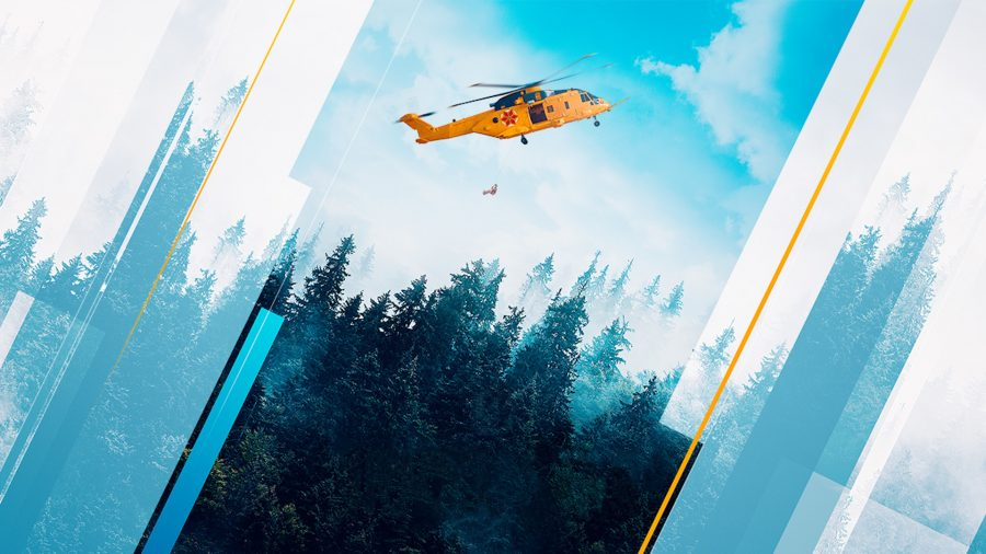 An orange helicopter flying high above a forest while someone hangs off a wire