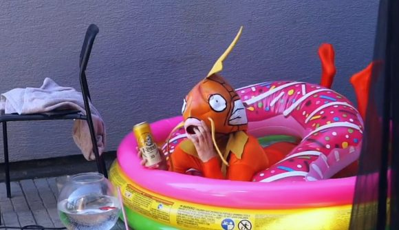 A Twitch streamer wearing a Magikarp costume, holding a beer, while sitting in a paddling pool