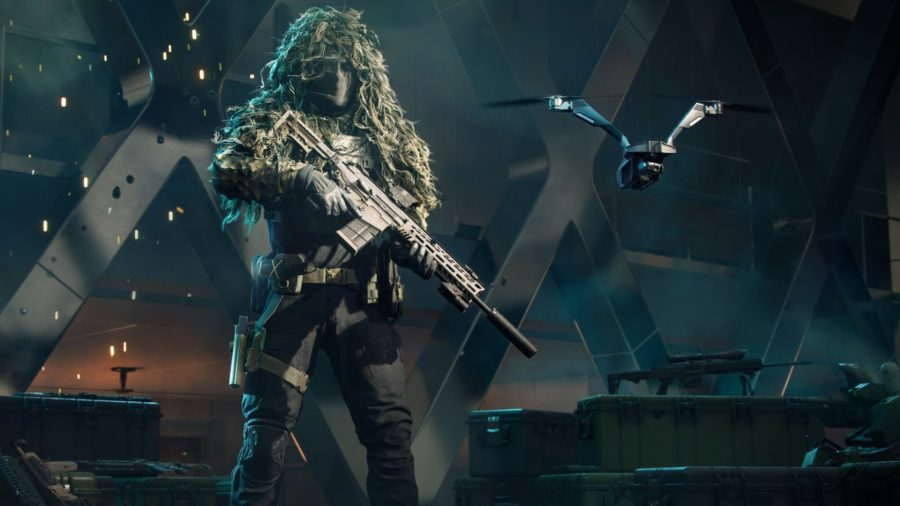 A specialist wearing camouflage gear stands holding a weapon, next to a hovering drone