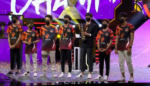 A team collects their trophy on stage at a Free Fire tournament