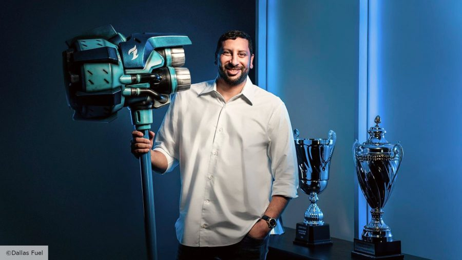 Founder of Team Envy, hastro, poses with a giant hammer in front of two esports trophies