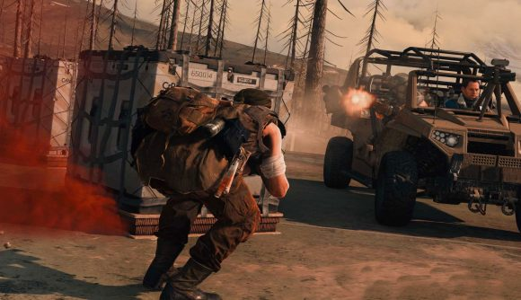 A Warzone operator crouches for cover behind a loadout drop, while and enemy team in buggy open fire