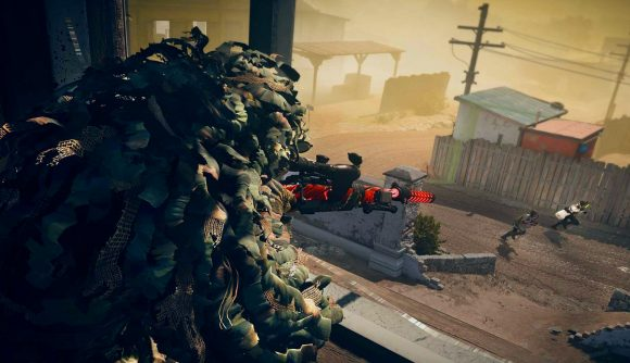A sniper wearing a ghillie suit aims in on two operators running along the street below