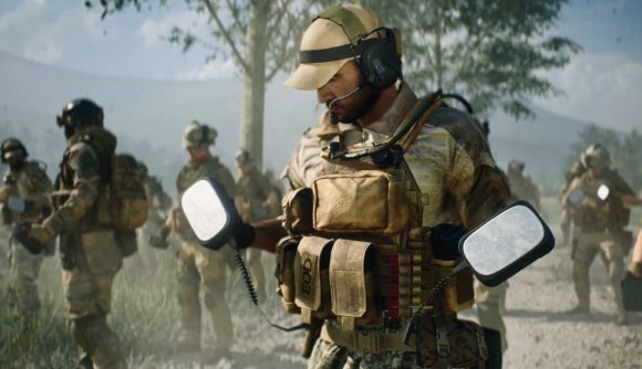 A US soldier wearing a baseball cap looks at the defibrillator he's holding