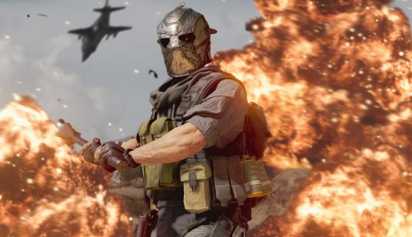 A Black Ops Cold War operator, wearing a silver full-face helmet and holding a large mace, stands in front of a massive explosion