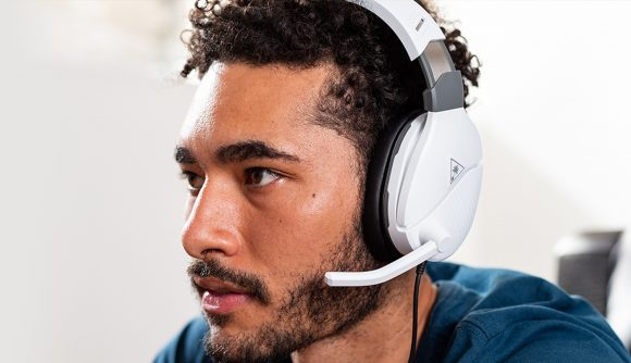 A slightly bearded man wearing a white headset with a mic sticking off it