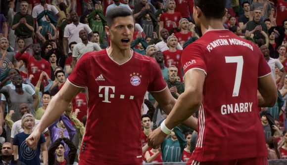 Robert Lewandowski, wearing a red Bayern Munich kit, celebrates a goal with another player in front of a crowd