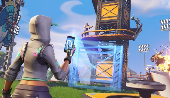 A player in a white hoodie holds up a phone in front of a recently constructed tower in Fortnite