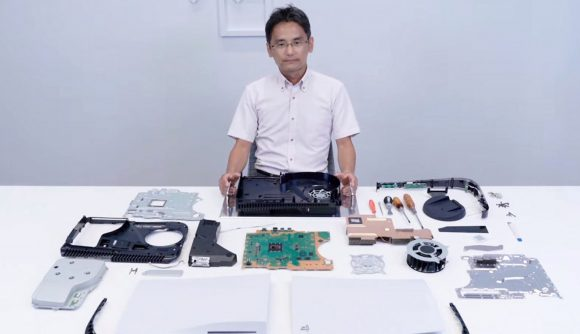 A Sony engineer sits at a desk with a PS5 taken apart in front of him