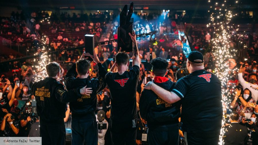 The Atlanta FaZe Call of Duty team hoist the CDL trophy in the air, with their backs to the camera. In the background, a crowd of people cheer