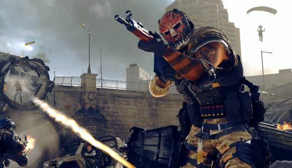 A Warzone operator in a red mask aims a C58 assault rifle while a battle ensues behind him. One player is firing a rocket launcher, and another is parachuting through the air