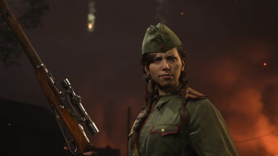 A female soldier in a dark green military uniform holds her sniper rifle in one hand, pointing it towards the sky