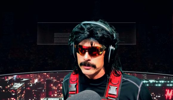 Dr Disrespect, wearing his signature sunglasses, moustache, and red combat vest, in front of his streaming microphone