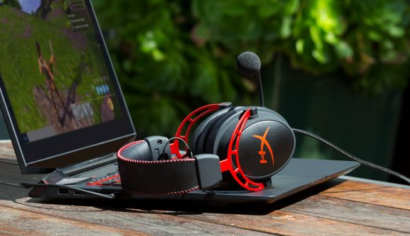 A pair of black and red gaming headphones sitting on top of a laptop which has a game of Fortnite on the display