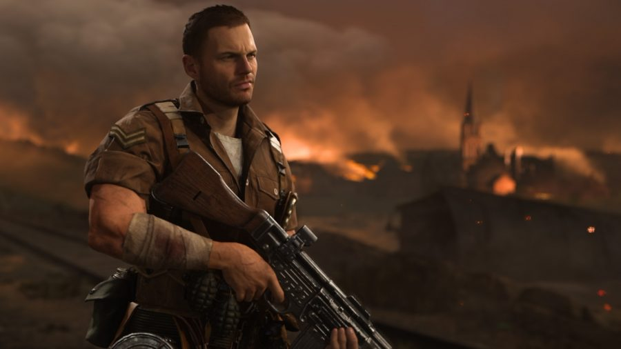 A amle soldier weating a brown military uniform holds an LMG while a fire rages behind him