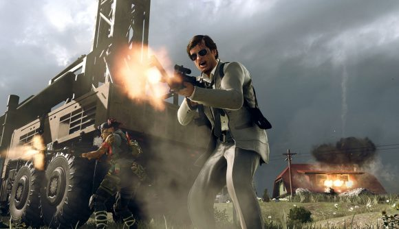 Adler in a white suit screams as he fires a gun in front of a Warzone Mobile station