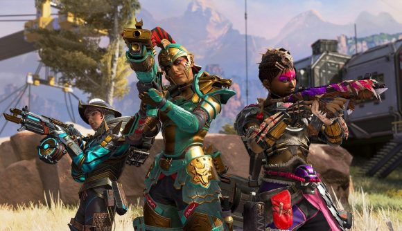 Three female Apex Legends characters wearing colourful armour stand in a semi circle aiming their guns