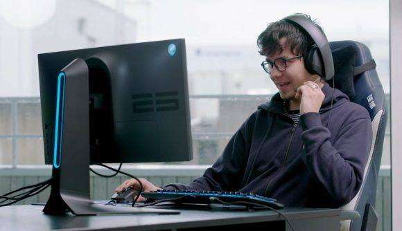 Asa Butterfield talks into a gaming mic while playing Dota 2 on a Alienware computer