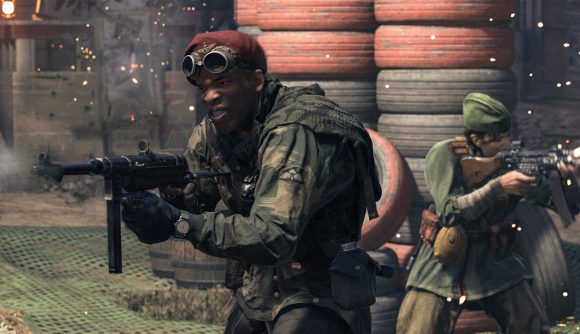 A soldier in a red beret and green military gear grits his teeth as he fires a submachine gun