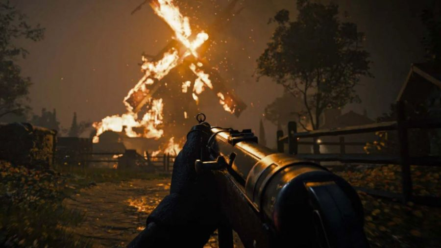 A soldier with an MP40 stares at a burning windmill.