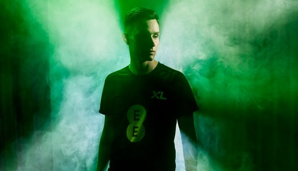 FIFA pro Tom Leese wearing a black Excel Esports jersey, surrounded by smoke and green lighting