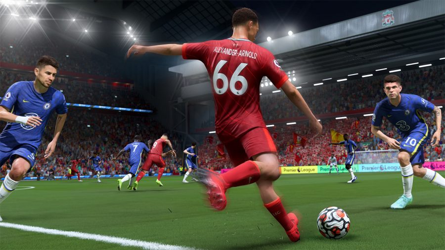 A Liverpool player in a red kit looks to cross the ball while being closed down by two Chelsea players in blue